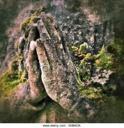 let-us-pray-clasped-hands-of-an-old-stone-statue-covered-with-moss-s0b6cn